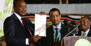 President-elect Uhuru Kenyatta displays the presidential results certificate after receiving it from IEBC chairman Isaack Hassan at the Bomas of Kenya, Nairobi March 9, 2013.